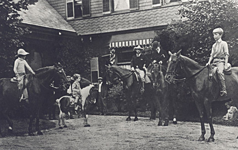 Astride a horse and wearing her black riding derby, Edith Roosevelt with her husband and sons Quention, Archie and Kermit at the front of their home Sagamore Hill. (NPS)