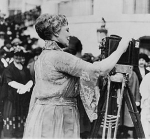 First Lady Florence Harding cranks out a newsreel camera before a group of women press. (LIbrary of Congress