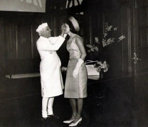 "Jacqueline Kennedy permits India's Prime Minister to place a traditional Hindu ""talik"" symbol on her forehead, during her 1962 tour of that nation. (JFKL)"