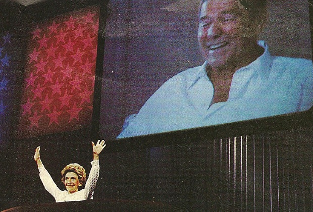 Nancy Reagan on the podium, her husband on the screen behind her.