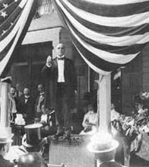 "William McKinley delivers a speech from the front-porch of ""Campaign House,"" while Ida McKinley listens, while seated at far right. (Harper's Magazine)"