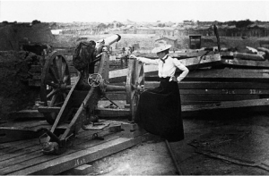 Lou Hoover inspecting one of the cannons at a Chinese fort that shelled the community of Tientsin during the Boxer Rebellion, 1900.