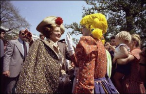A color photo showing Betty Ford permitting a clown to apply some makeup to her face at the 1975 Easter Egg Roll. (Ford Library)
