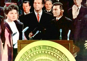 A fictional first woman President takes the oath of office as a fictional First Gent looks on.