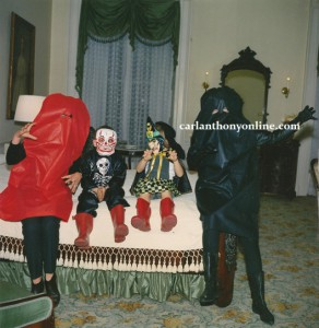 Jacqueline Kennedy in Halloween costume seated on the Lincoln bed, with her daughter, nephew and sister-in-law Jean Smith.