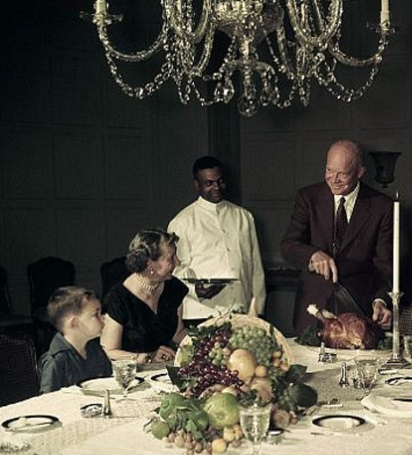 Mamie Eisenhower looks on smilingly, beside her grandson, as the President carves a Thanksgiving turkey. (Wide World)