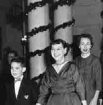 Seen here with her grandson  and daughter-in-law Mamie Eisenhower had the Cross Hall columns wrapped in evergreen garland.
