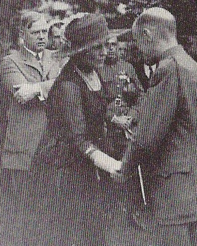 First Lady Florence Harding welcomes a wounded World War I veteran as Charles Forbes, arms crossed, stands behind her.