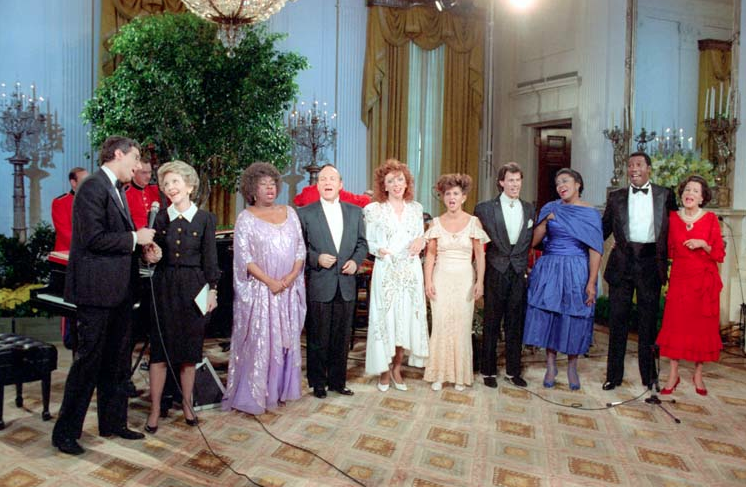 "Nancy Reagan, Marvin Hamlisch, Kitty Carlisle, Sarah Vaughn, the Manhattan Transfer, George Merritt and Priscilla Baskerville during an In Performance at the White House, ""Tribute to American Music"" in East Room, October 26, 1986. (RRPL)"