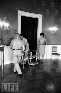 Mrs. Kennedy moving furnishings with federal government maintenance personnel in the Blue Room. (Life)