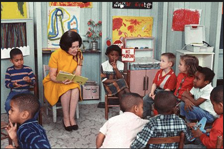 "Lady Bird Johnson's other most familiar role in the public's mind was being the human face of LBJ's ""War on Poverty"" social legislation, most prominently as a key promoter of Head Start. The now seemingly requisite photos of First Ladies sitting on small plastic grade school chairs and reading books to children began with Mrs. Johnson. (LBJL)"
