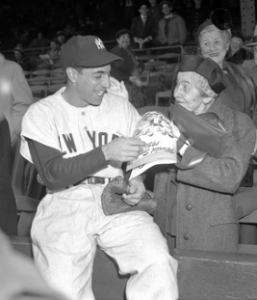 Phil Rizzuto gives the elderly Mrs. Coolidge an autograph at the 1950 World Series. (sbnation.com)