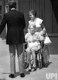 A nurse pushes Bess Truman in a wheelchair while the presidential widow's Secret Service agent looks on. (UPI)