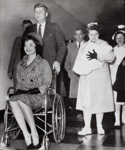 Jackie Kennedy being wheeled out of the hospital by her husband, the president-elect after giving north to their son by cesarian surgery. (ICP)