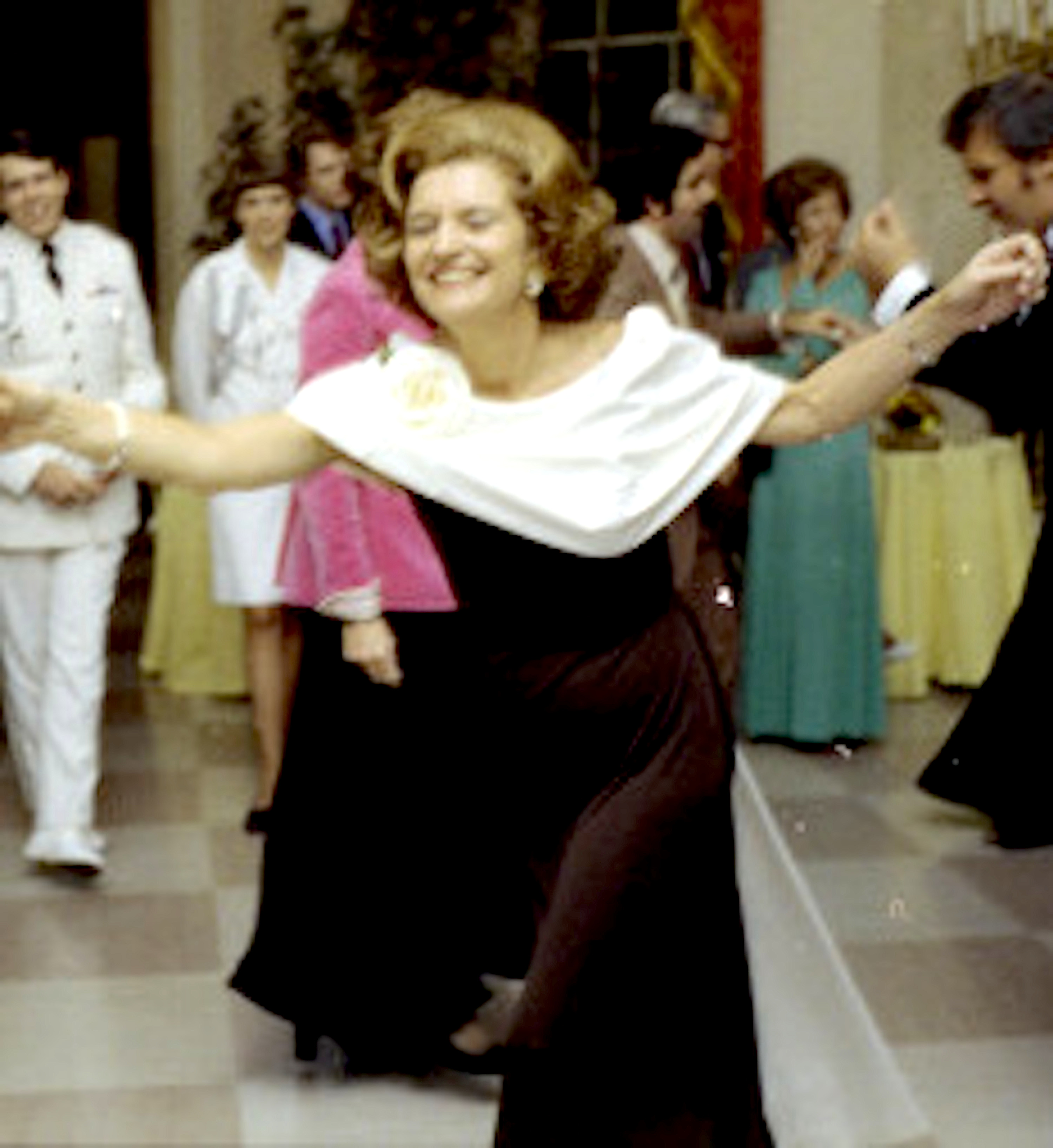 Betty Ford dancing at an October 1975 state dinner in a black gown with white caped collar. (GRFL)